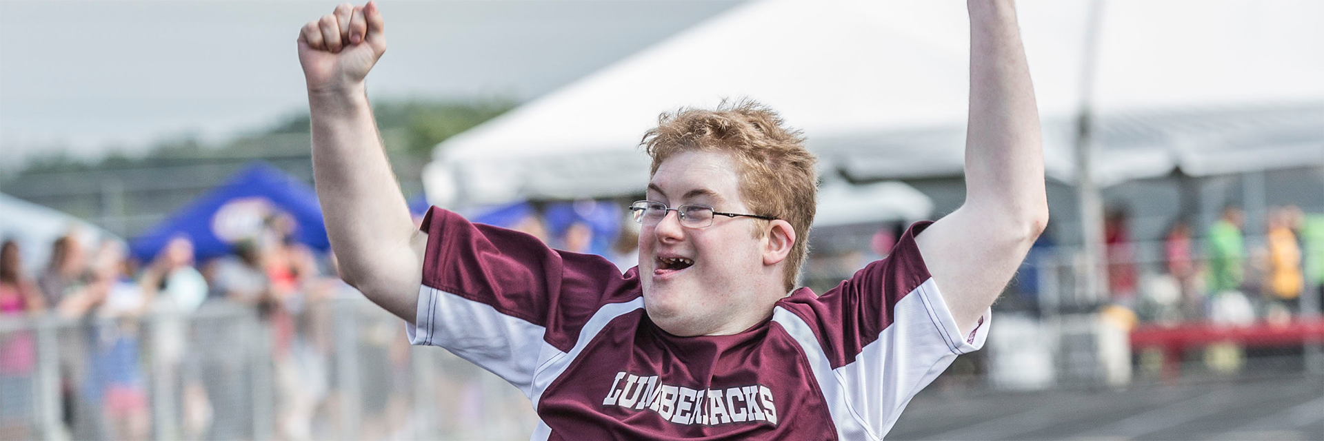 Special Olympics Minnesota athlete smiling and celebrating with arms up