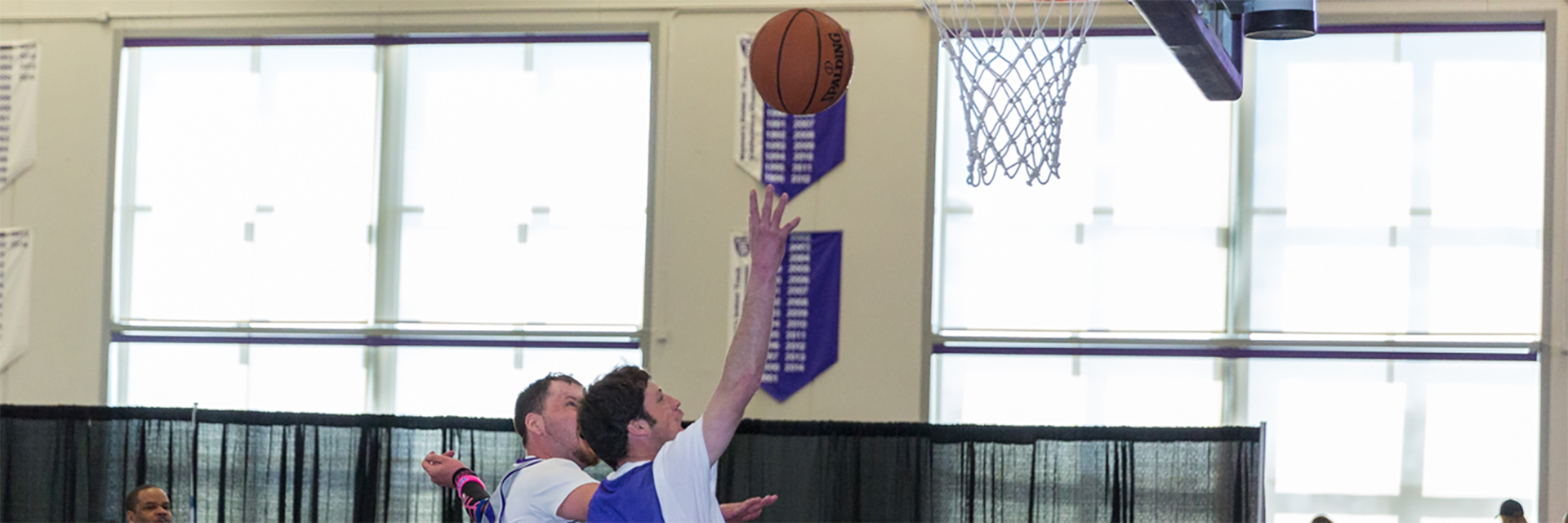 Special Olympics Minnesota basketball athlete shooting ball while another athlete watches from behind
