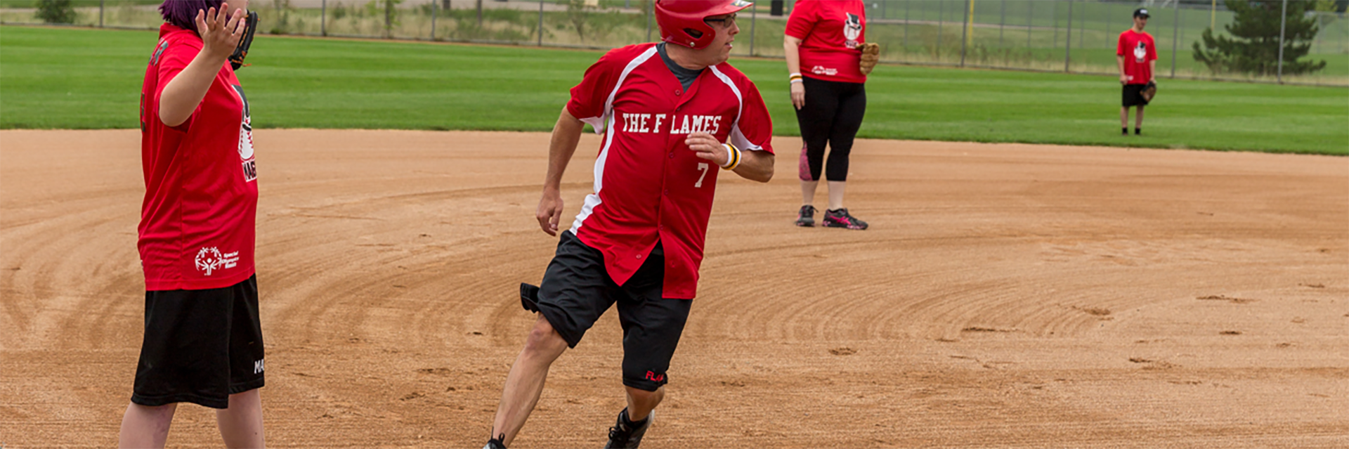 Special Olympics Minnesota softball athlete running bases during game with coach and other athletes in background