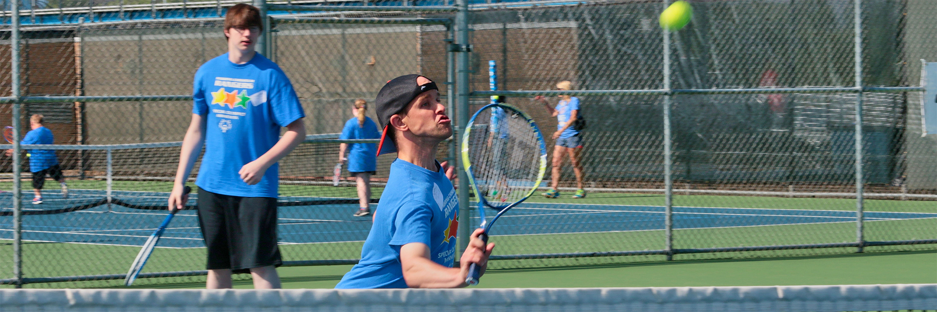 Special Olympics Minnesota tennis athlete preparing to hit tennis ball while teammate watches from behind